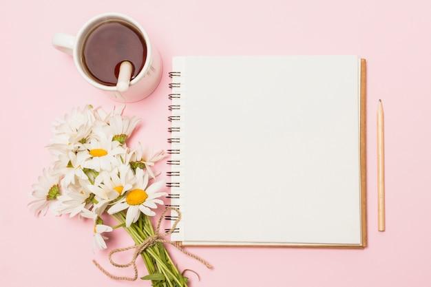 Cuaderno cerca de flores y copa de bebida.