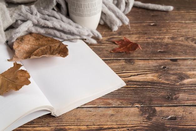 Cuaderno cerca de hojas de otoño y bufanda sobre mesa