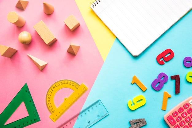 Cuaderno cerca de materiales matemáticos