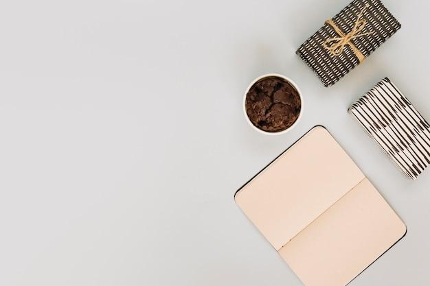 Cuaderno cerca de muffins y regalos