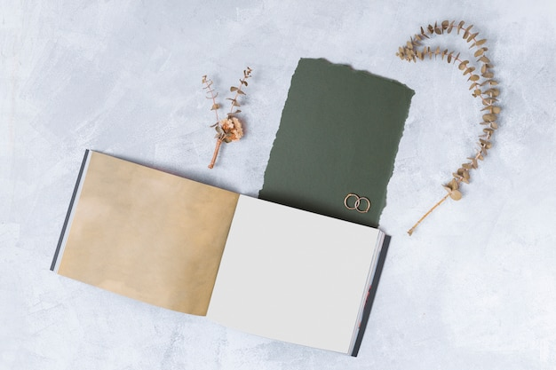 Cuaderno cerca de papel negro y ramitas de plantas secas.