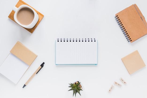 Cuaderno cerca de papelería, taza de café y macetas
