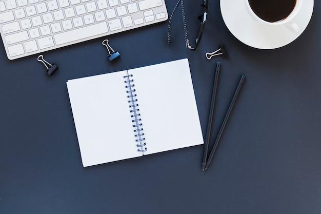 Cuaderno cerca de papelería, teclado y juego de té