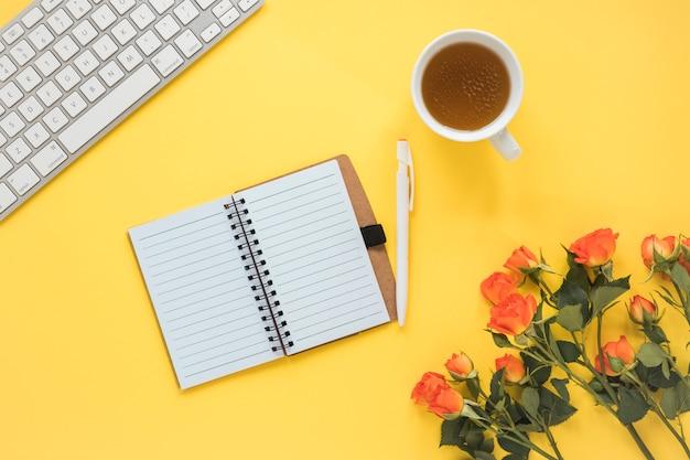 Cuaderno cerca de taza de bebida, teclado y rosas frescas con hojas verdes