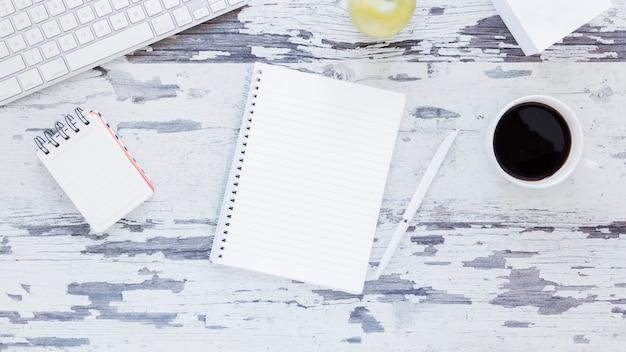 Cuaderno cerca del teclado y la taza de café en la mesa sucia