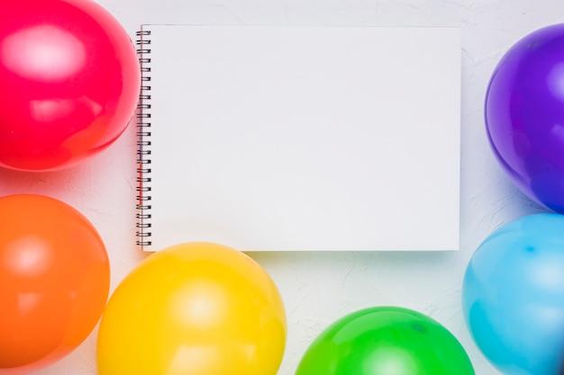 Cuaderno claro y globos de colores.
