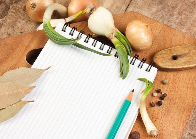 Cuaderno para cocinar recetas y especias en una mesa de madera