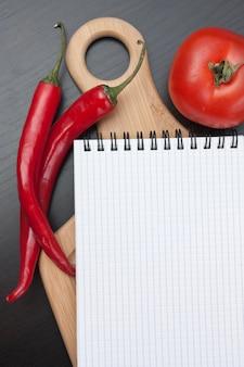 Cuaderno para cocinar recetas y verduras en una tabla de cortar