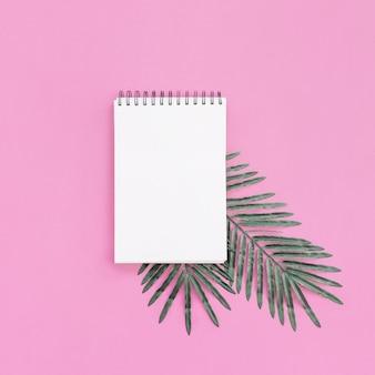 Cuaderno con hojas de palma sobre fondo rosa para maqueta