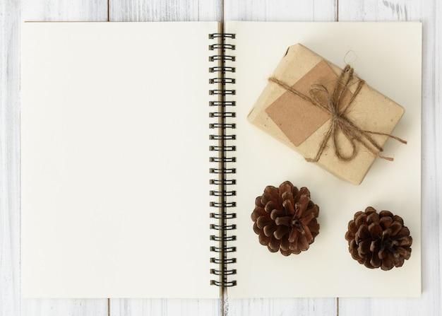 Cuaderno, cono de pino y caja de regalo pacel marrón sobre fondo de mesa de madera blanca