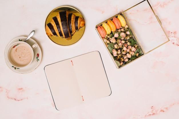 Cuaderno con croissant y caja con flores en mesa