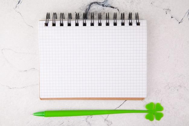 Cuaderno cuadrado sobre un fondo blanco, decoración para el día de san patricio.