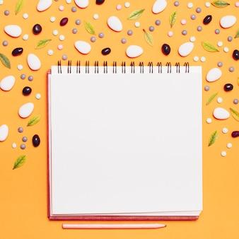 Cuaderno de cuadros rodeado de grageas y hojas.