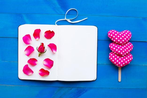 Cuaderno del diario con los corazones de la rosa y de la tarjeta del día de san valentín en fondo de madera azul.