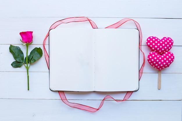 Cuaderno del diario con los corazones de la rosa y de la tarjeta del día de san valentín en el fondo de madera blanco.