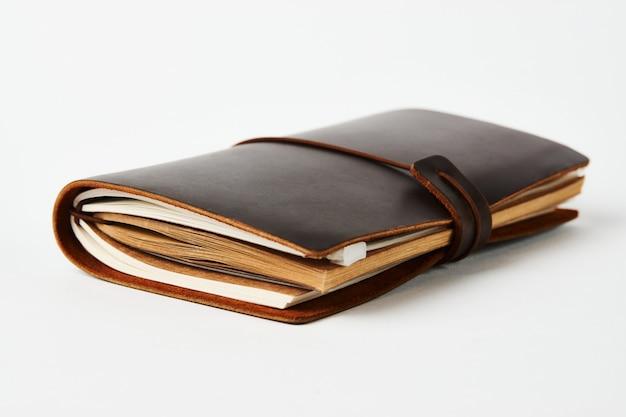 Cuaderno diario de papel hecho a mano en cubierta de cuero marrón, primer plano.