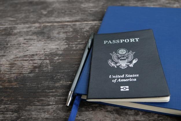 Cuaderno del diario del pasaporte y pluma con fondo de madera