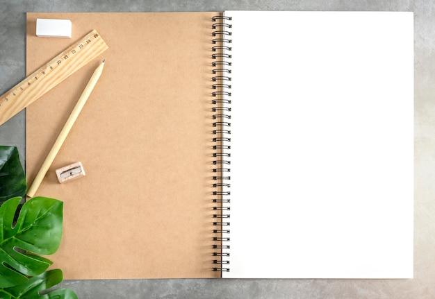 Cuaderno de dibujo en blanco y hojas verdes