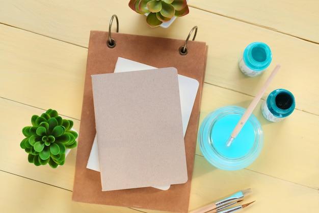 Cuaderno de dibujo en blanco, lápices, pinceles y pinturas sobre fondo de madera amarilla