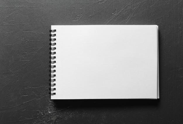 Cuaderno de dibujo en blanco con páginas blancas aisladas sobre fondo negro
