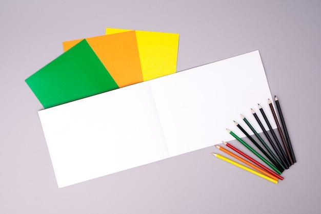 Cuaderno de dibujo con lápices de colores y papel de color sobre gris.