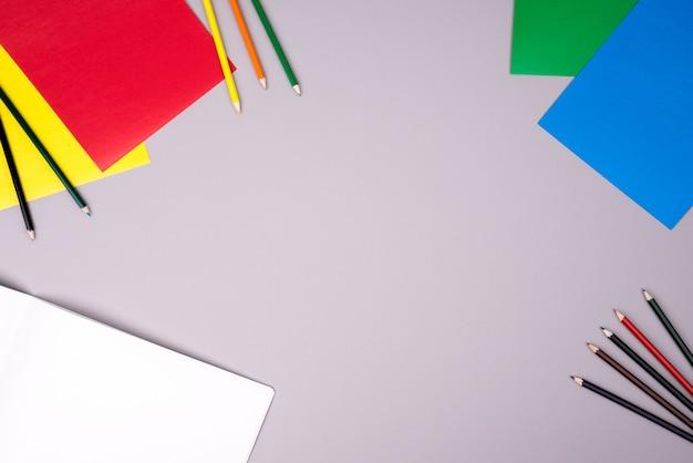 Cuaderno de dibujo, lápices de colores y papel de colores.