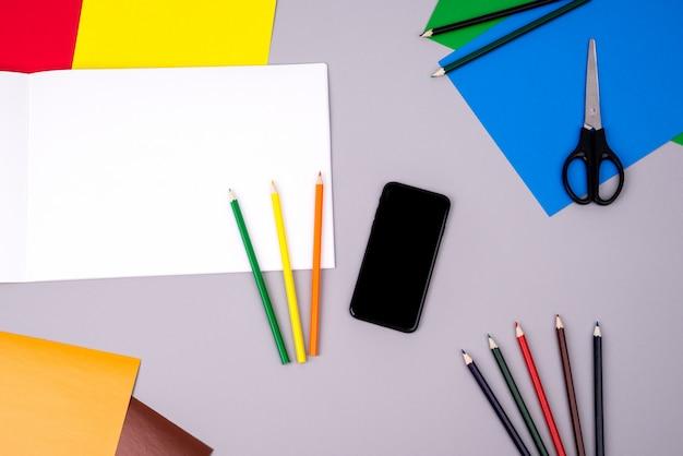 Cuaderno de dibujo con lápices de colores, teléfono móvil y papel de color en gris.