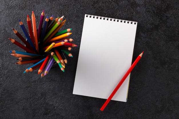 Cuaderno de dibujo y lápices de colores.