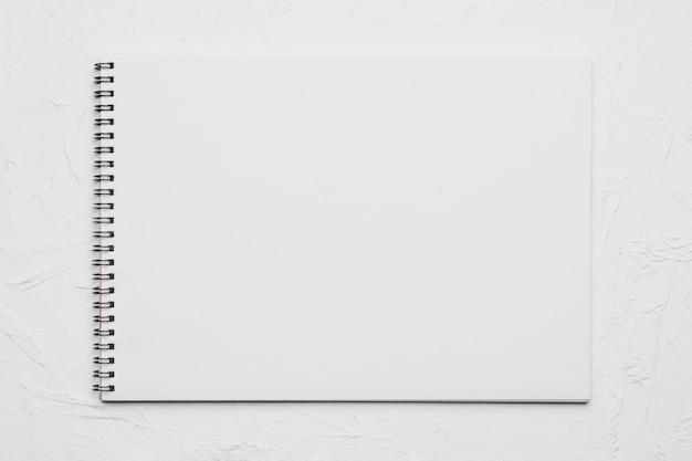 Cuaderno de dibujo vacío blanco sobre superficie rugosa