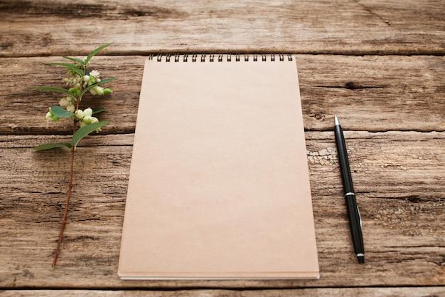 Cuaderno de dibujo vintage con pluma y flor