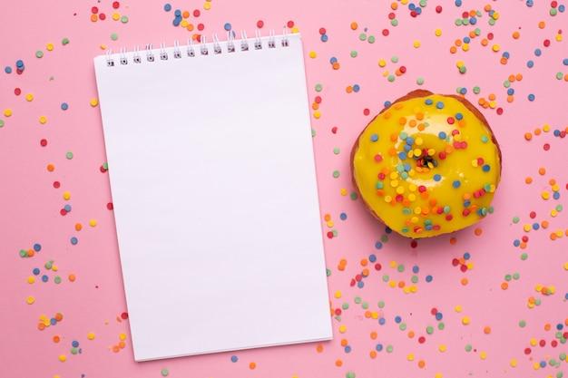 Cuaderno y donut dulce amarillo sobre un fondo rosa plano lay
