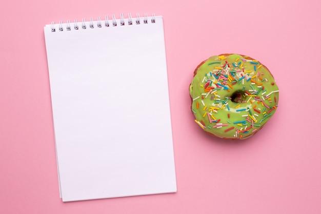 Cuaderno y dulce donut verde con espolvorear sobre un fondo rosa plano lay