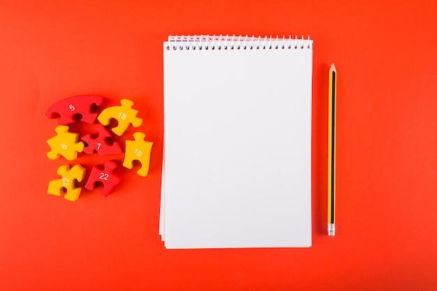 Cuaderno en blanco con rompecabezas en la mesa