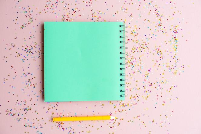 Cuaderno en blanco y bolígrafo con confeti