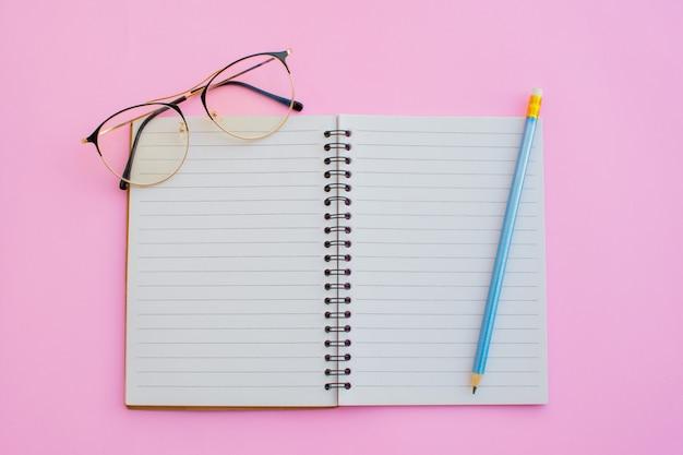 Cuaderno y equipo de regreso a la escuela sobre fondo de color.