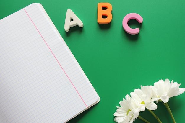 Cuaderno escolar junto a las letras abc y crisantemos blancos.
