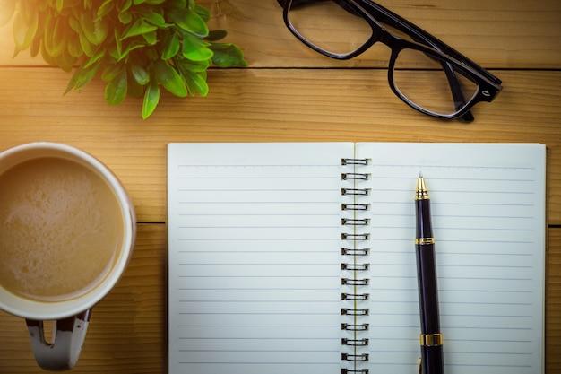 Cuaderno escolar con páginas en blanco y con vasos junto a una taza de café en la mesa de madera