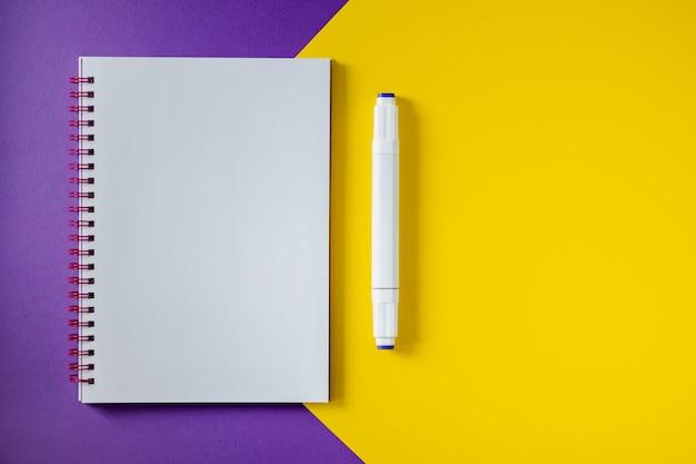 Cuaderno de la escuela en amarillo y púrpura, libreta espiral en una tabla. fondo de la vista superior con copyspace. bloc de notas de oficina plano.