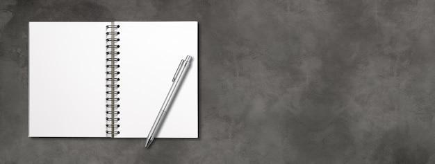 Cuaderno espiral abierto en blanco y bolígrafo aislado en hormigón oscuro