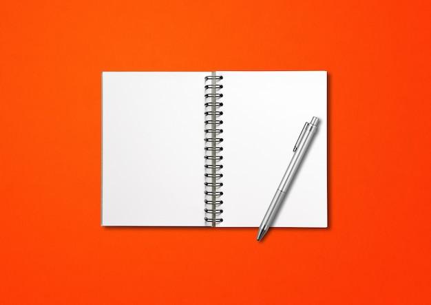 Cuaderno espiral abierto en blanco y bolígrafo aislado en rojo
