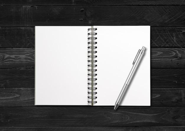 Cuaderno espiral abierto en blanco y bolígrafo aislado sobre fondo de madera negra