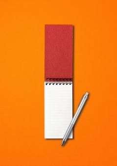 Cuaderno espiral abierto en blanco y maqueta de bolígrafo aislado en naranja