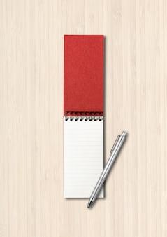 Cuaderno espiral abierto en blanco y maqueta de bolígrafo aislado sobre fondo blanco de madera