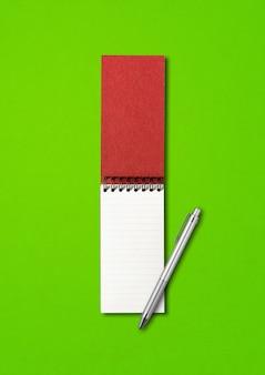 Cuaderno espiral abierto en blanco y maqueta de bolígrafo aislado en verde