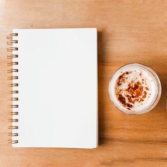 Cuaderno espiral blanco cerrado y vaso de café con cacao en polvo.