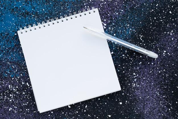 Cuaderno espiral en blanco con espacio de copia de texto sobre fondo azul oscuro abstracto. concepto de planificación. página de papel blanco y bolígrafo, hoja vacía, maqueta.