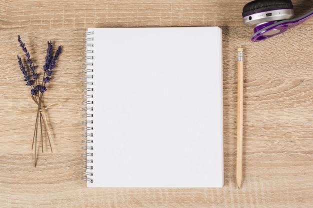 Cuaderno espiral en blanco; lápiz; auriculares y ramitas de lavanda sobre fondo de madera