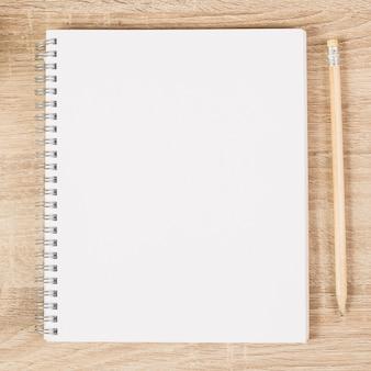 Cuaderno espiral en blanco y lápiz de madera en escritorio de madera