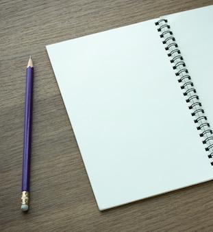 Cuaderno espiral en blanco y lápiz sobre fondo de madera oscura