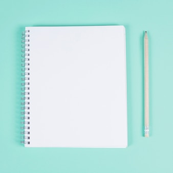 Cuaderno espiral en blanco con lápiz sobre fondo turquesa